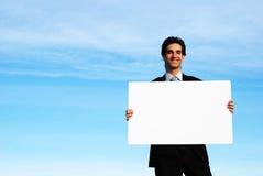 Homme d'affaires retenant le panneau blanc photographie stock