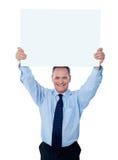 Homme d'affaires retenant un panneau-réclame blanc Image libre de droits