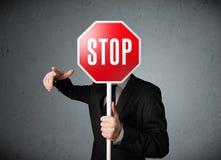 Homme d'affaires retenant un signe d'arrêt Images stock