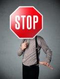 Homme d'affaires retenant un signe d'arrêt Image stock