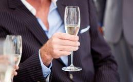Homme d'affaires retenant une glace de Champagne Photographie stock libre de droits