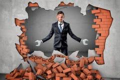 Homme d'affaires robotisé avec des mains de clé cassant le mur de briques rouge sur le fond gris illustration libre de droits