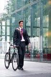 Homme d'affaires roulant une bicyclette par la ville Images stock