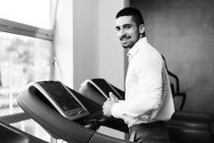 Homme d'affaires Running On Treadmill dans le gymnase photographie stock libre de droits