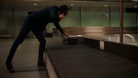 Homme d'affaires sélectionnant son bagage du secteur 4k de retrait des bagages banque de vidéos