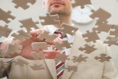 Homme d'affaires séparant le puzzle images stock