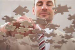 Homme d'affaires séparant le puzzle Photographie stock libre de droits