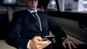 Homme d'affaires sérieux à l'aide du téléphone dans la voiture, appli pour analyser des embouteillages dans la ville images libres de droits