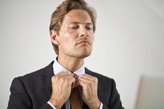 Homme d'affaires sérieux ajustant le lien Photos stock