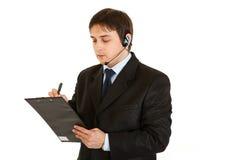 Homme d'affaires sérieux avec l'écouteur et la planchette image stock