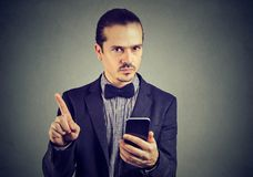Homme d'affaires sérieux avec le smartphone ne montrant aucune attention avec le doigt photo stock