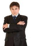 Homme d'affaires sérieux avec les bras croisés sur le coffre Image stock