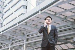 Homme d'affaires sérieux avec parler de smartphone Photos stock