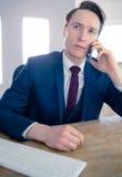 Homme d'affaires sérieux ayant un appel téléphonique Photo stock