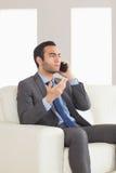 Homme d'affaires sérieux ayant un appel téléphonique se reposant sur le sofa confortable Photographie stock libre de droits
