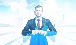 Homme d'affaires sérieux contre le paysage urbain avec des flèches et des graphiques Photo stock