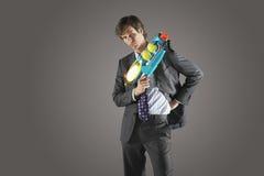 Homme d'affaires sérieux Holding Water Gun Photographie stock