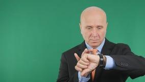 Homme d'affaires sérieux Image Looking à la montre-bracelet image stock