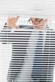Homme d'affaires sérieux jetant un coup d'oeil par des abat-jour dans le bureau Photo libre de droits