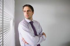 Homme d'affaires sérieux jetant un coup d'oeil par des abat-jour dans le bureau Images stock