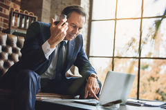 Homme d'affaires sérieux mûr utilisant l'ordinateur portable Photos libres de droits