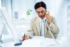Homme d'affaires sérieux parlant au téléphone image stock