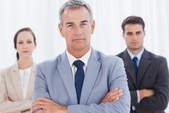 Homme d'affaires sérieux posant avec son équipe de travail photos libres de droits