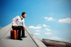 Homme d'affaires sérieux s'asseyant sur son sac Image libre de droits
