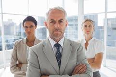 Homme d'affaires sérieux se tenant devant des collègues images stock