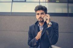 Homme d'affaires sérieux sur la rue parlant au téléphone portable images stock