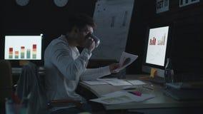 Homme d'affaires sérieux travaillant sur l'ordinateur dans le bureau de nuit banque de vidéos
