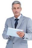 Homme d'affaires sérieux utilisant le comprimé numérique Images libres de droits