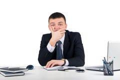 Homme d'affaires sérieux vous regardant avec scepticisme s'asseyant à son bureau d'isolement sur le fond blanc Expression de visa Photo libre de droits