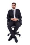 Homme d'affaires sévère s'asseyant sur une chaise de bureau image libre de droits