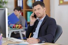 Homme d'affaires sûr avec le téléphone dans le bureau Photos libres de droits