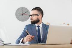 Homme d'affaires sûr regardant le travail parti le lieu de travail avec l'ordinateur portable Images stock