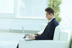Homme d'affaires sûr travaillant sur l'ordinateur portable se reposant dans le bureau spacieux Photos libres de droits