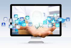 Homme d'affaires s'échappant à partir de l'ordinateur tenant l'ampoule et numérique Photographie stock libre de droits
