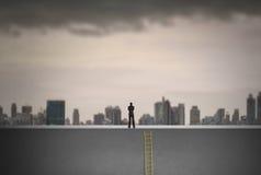 Homme d'affaires s'élevant sur l'échelle au-dessus de la ville pensant à l'avenir, concept de direction Photo stock