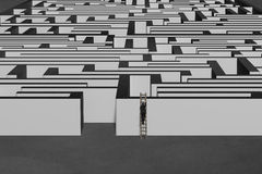 Homme d'affaires s'élevant sur l'échelle en bois jusqu'au dessus du mur de labyrinthe Image libre de droits