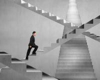 Homme d'affaires s'élevant sur le labyrinthe concret d'escalier Photo libre de droits