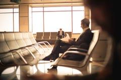 Homme d'affaires s'asseyant à l'aéroport, attendant son vol Photographie stock libre de droits