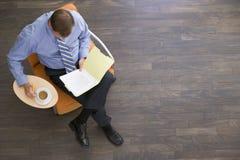 Homme d'affaires s'asseyant à l'intérieur avec du café et le dépliant Images libres de droits