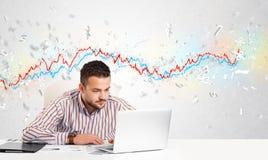 Homme d'affaires s'asseyant à la table avec le marché boursier Photos stock