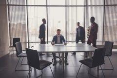 Homme d'affaires s'asseyant à la table avec travailler les personnes brouillées sur le fond Photo libre de droits