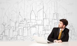 Homme d'affaires s'asseyant à la table blanche avec les bâtiments tirés par la main Image stock