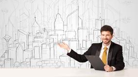 Homme d'affaires s'asseyant à la table blanche avec les bâtiments tirés par la main Photo stock