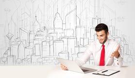 Homme d'affaires s'asseyant à la table blanche avec les bâtiments tirés par la main Photos stock