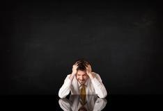 Homme d'affaires s'asseyant à un bureau image stock