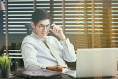 Homme d'affaires s'asseyant au bureau avec l'ordinateur portable photographie stock